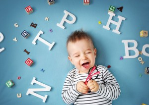 56033302 - one year old child lying with spectacles and letters on blue background