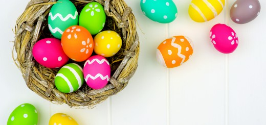 Springtime nest with colorful Easter Eggs against a white wood background
